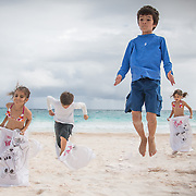 kids on the beach,beach games,children,sand,ocean,sack race,jumping