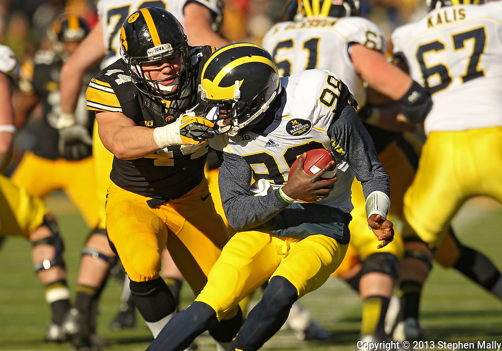 November 23 2013: Iowa Hawkeyes linebacker James Morris (44) tries to pull down Michigan Wolverines quarterback Devin Gardner (98) during the third quarter of the NCAA football game between the Michigan Wolverines and the Iowa Hawkeyes at Kinnick Stadium in Iowa City, Iowa on November 23, 2013. Iowa defeated Michigan 27-24. Iowa defeated Michigan 24-21.