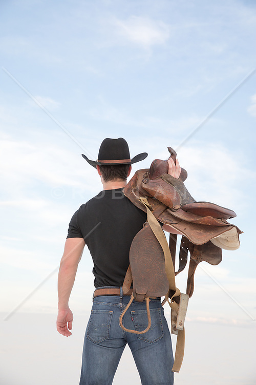 cowboy walking with a saddle over his shoulder