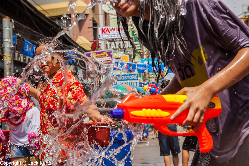 """13 APRIL 2013 - BANGKOK, THAILAND:  Thais and foreign tourists participate in water fights up and down Khao San Road, which is Bangkok's """"backpacker"""" district, during Songkran celebrations in the Thai capital. Songkran is celebrated in Thailand as the traditional New Year's Day from 13 to 16 April. The date of the festival was originally set by astrological calculation, but it is now fixed. If the days fall on a weekend, the missed days are taken on the weekdays immediately following. Songkran is in the hottest time of the year in Thailand, at the end of the dry season and provides an excuse for people to cool off in friendly water fights that take place throughout the country. Songkran has been a national holiday since 1940, when Thailand moved the first day of the year to January 1.   PHOTO BY JACK KURTZ"""