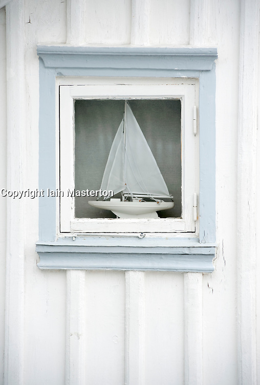 Detail of sailing boat in window of wooden house in village of Fiskebackskil  on Bohuslan coast in Vastra Gotaland Sweden