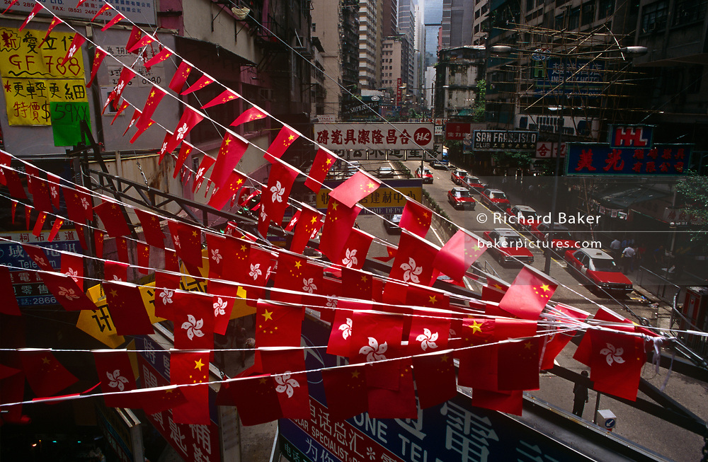 The flags of Hong Kong and Peoples' Republic of China fly together above the streets of Central, the day after the Handover of sovereignty from Britain to China, on 30th June 1997, in Hong Kong, China. Midnight signified the end of British rule, and the transfer of legal and financial authority back to China. Hong Kong was once known as 'fragrant harbour' (or Heung Keung) because of the smell of transported sandal wood.