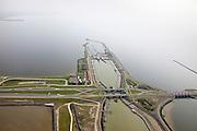 Nederland, Friesland, Gemeente Wonseradeel, 28-04-2010; Afsluitdijk ter hoogte van Kornwerderzand, gezien naar de kust van Friesland. Op het voormalig werkeiland liggen de Lorentzsluizen, een complex van spuisluizen en schutsluizen. De spuisluizen (uitwaterende sluizen lozen van het IJsselmeer op de Waddenzee (li). De sluizen worden beschermd door kazematten (bunkers). .Enclosure Dam at the height of Kornwerderzand seen in the direction of the coast of Friesland. On teh former work island the Lorentz locks, a complex of sluices and locks. The sluices sluice surplus water to the Wadden sea (l). The locks are protected by bunkers..luchtfoto (toeslag), aerial photo (additional fee required).foto/photo Siebe Swart