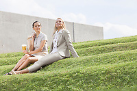 Full length of relaxed businesswomen sitting on grass steps against sky