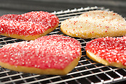 Heart shaped sugar cookies with white, pink, and red sugar sprinkles.