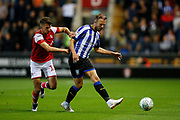 Jordan Rhodes of Sheffield Wednesday plays the ball with Daniel Barlaser of Rotherham United chasing down during the EFL Cup match between Rotherham United and Sheffield Wednesday at the AESSEAL New York Stadium, Rotherham, England on 28 August 2019.