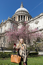 © Licensed to London News Pictures. 05/04/2018. London, UK. A woman takes a photograph in front of cherry blossom next to St Paul's Cathedral in London during sunny spring weather today. Photo credit: Vickie Flores/LNP