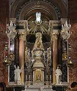 Statue of Our Lady of the Forsaken, patroness of Valencia, in the Real Basilica de nuestra Senora de los Desamparados de Valencia, a Baroque church designed by Diego Martinez Ponce de Urrana and built 1652-67, in Valencia, Spain. The 15th century Gothic statue is covered in robes and jewels and the 2 innocents at her feet were added in the 18th century. The statue stands on a mechanical device which slowly revolves. On the Festival of Our Lady in May, the statue is paraded around the town. The confraternity of the Mare de Deu dels Innocents i Desemparats was founded in the 15th century to help the mentally ill and to bury their bodies. Picture by Manuel Cohen