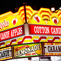 Picture of couty fair concession stand food sign at night with lemonade, cotton candy, popcorn, and candy apples.  Also commonly seen at carnivals, amusement parks and festivals. Photo is high resolution.