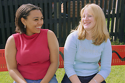 Two young women sitting on bench in children's playground laughing,