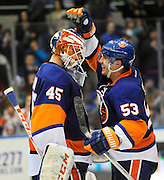 New York Islanders' Casey Cizikas (53) congratulates goalie Anders Nilsson (45) after the Islanders defeated the Buffalo Sabres 4-1 in an NHL hockey game on Saturday, March 15, 2014, in Uniondale, N.Y. (AP Photo/Kathy Kmonicek)