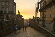 SANTIAGO DE COMPOSTELA, SPAIN - 15th October 2017 - Pilgrim tourists and travelers who are walking the Camino de Santiago (Way of St.James) walk through Praza do Obradoiro at sunset, Santiago de Compostela, Galicia, Spain.