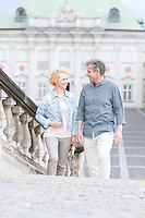 Happy middle-aged couple looking at each other while climbing steps