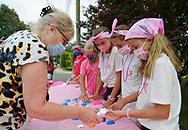 Merrick, New York, U.S. August 15, 2020. At left, KATHY DILLON, of Merrick, buys a shell ANNIE FITZPATRICK, 12, hands to her, during a Lizzie's Army fund raiser for money to donate to American Cancer Society Making Strides Against Breast Cancer. When Annie's 24-year-old sister Lizzie Fitzpatrick was diagnosed with Triple Negative Breast Cancer in late June, Annie, her cousin Maddy and best friend Isabelle formed Lizzie's Army. Over $3,000 has been raised so far through shell sales and GoFundMe.