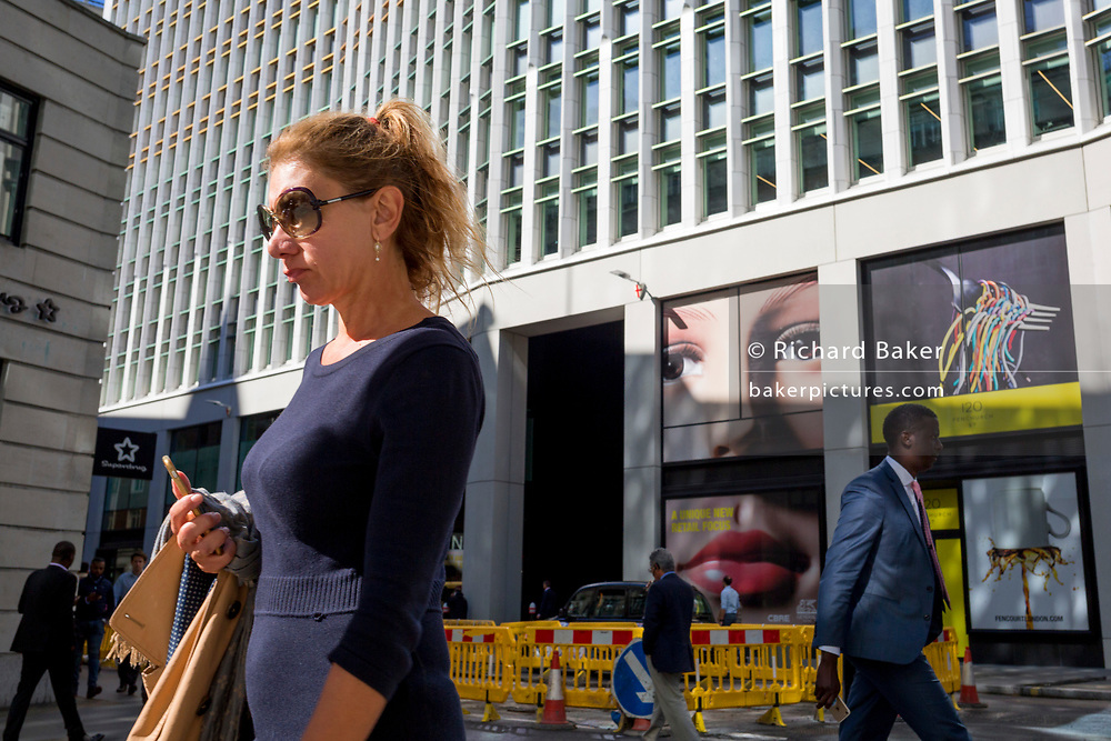 A pair of eyes and a lady passer-by on Fenchurch Street - in the heart of the capital's financial district (aka The Square Mile), on 24th September 2018, in London, England.