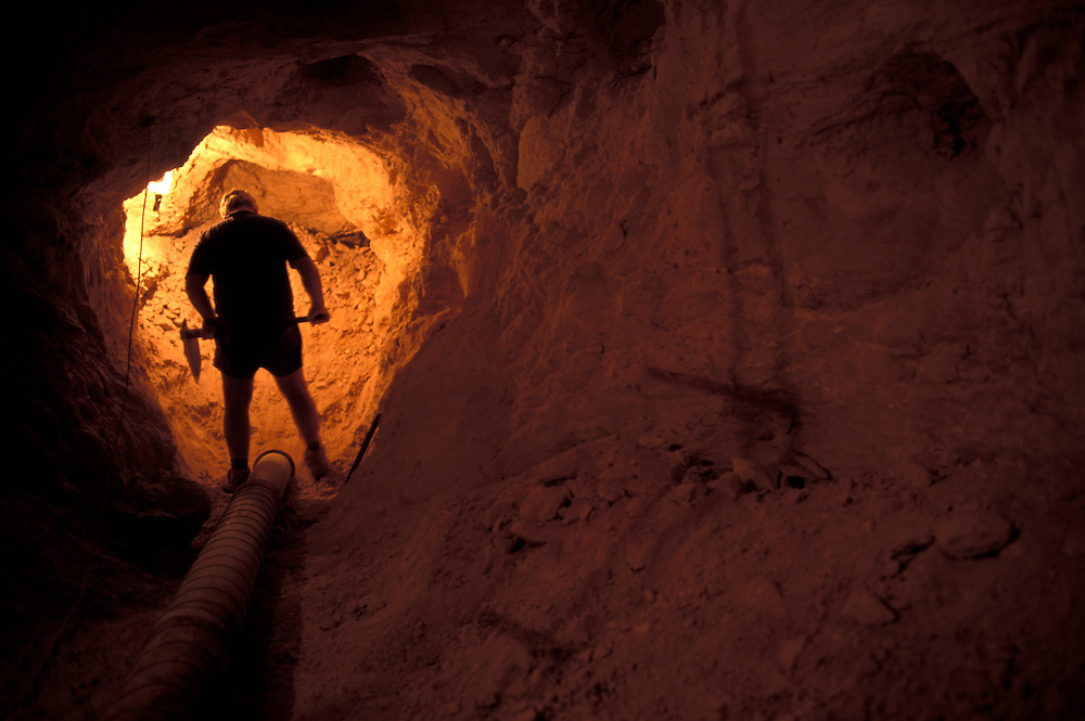 Australia, South Australia, (MR) Stuart Bird shovels through rubble while searching for opals in 100' deep mine in Coober Pedy.