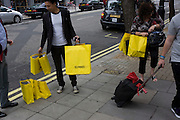 Shoppers carry their purchases in yellow Selfridges bags in London's West End. The bags are one of the capital's most striking symbols of British retail and are seen across the city as splashes of vibrant colour on the otherwise drab pavements and streets. The economic recovery appears to have begun in earnest and retail therapy has attracted these Londoners to the West End, away from the larger, warmer shopping Malls on the outskirts of town. Selfridges was founded by Harry Gordon Selfridge. The flagship store in London's Oxford Street is the second largest shop in the UK (after Harrods) and was opened on 15 March 1909.