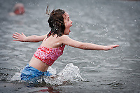 JEROME A. POLLOS/Press..Maggie Hurst, 8, explodes out of the 35-degree water of Lake Coeur d'Alene during the Polar Bear Plunge held Thursday at Sanders Beach. Hurst dove in by herself in order to receive 50 points from her second-grade teacher at Sorensen Magnet School.