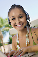 Woman Using Telephone Headset and Laptop