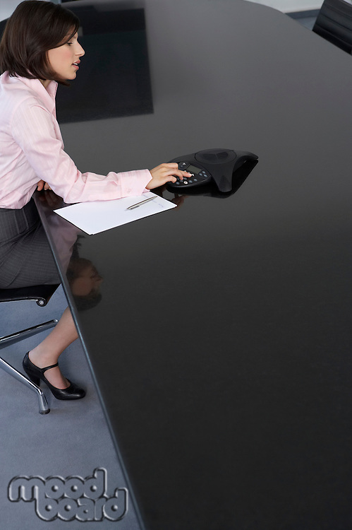 Business woman using calculator at conference room table