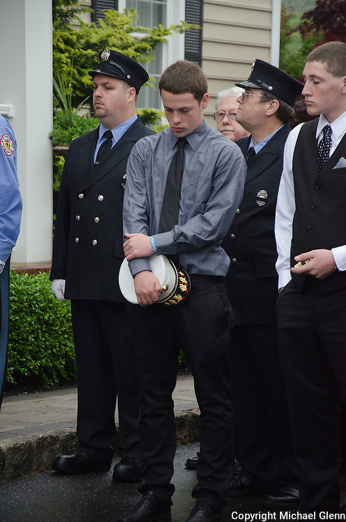 10Jun2013/Lanoka Harbor/NJ/USA/Fire chiefs son stands solemnly holding the hat his father wore