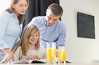 Happy parents assisting daughter in homework at home