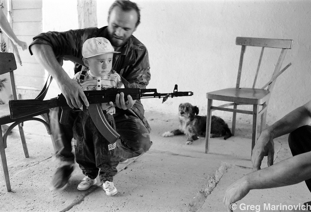 IPMG0866 Chechnya, 1995: A Chechen fighter tries to get a child to play with his Kalashnikov semi-automatic rifle in the liberated southern zone of Chechnya, July 1995.  Russia agreed to grant autonomy after Chechens retook several towns and the capital Grozny in 1995, after a bloody war for Chechen independence.  The Chechens are Moslem and have a strong sense of national identity.  Their fight for independence from Russia has increased an Islamic militancy and  identity. <br /> Photograph by Greg Marinovich/South Photographs