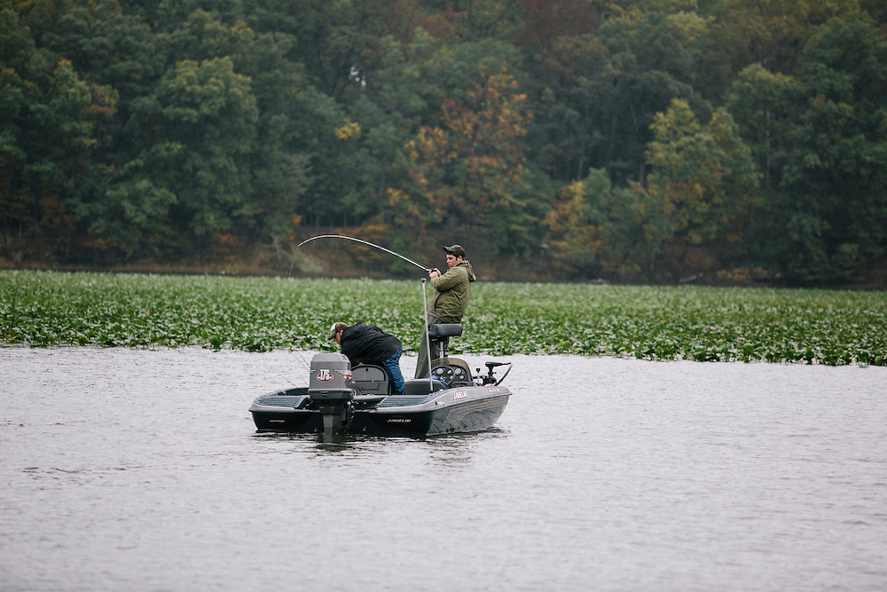 Seth Winslow, right, hauls in a bass as teammate Travis Riley, right, both of Christopher Newport University, assists during the FLW College Fishing Northern Conference Invitational in Marbury, MD on Oct. 11, 2014. Only the top 15 of 43 teams moved on to Sunday.