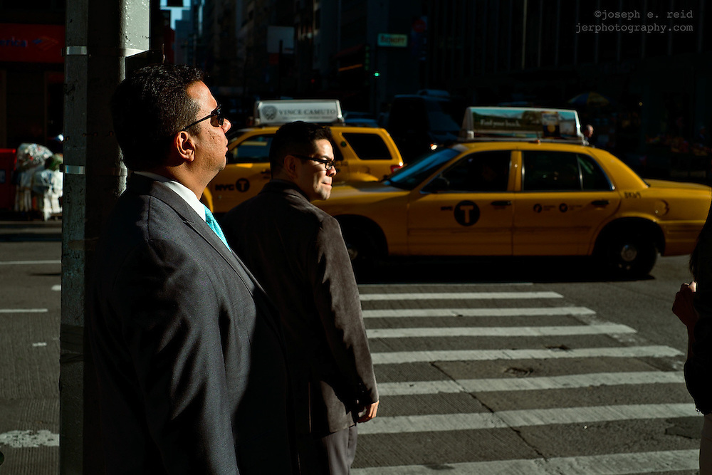 Two men waiting to cross 6th Avenue