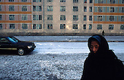 Pyongyang North Korea, Old lady walks past Mercedes Benz car in the snow
