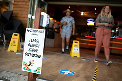 © Licensed to London News Pictures. 04/07/2020. Perranporth, UK. Social distancing guidelines are seen in the Watering Hole, (the UK's only bar on the beach) as it opens for the first time since the COVID-19 lockdown began. Today marks a lift in COVID-19 restrictions, as pubs are allowed to open, whilst customers must still follow social distancing guidelines. Tens of thousands of tourists are due to arrive in Cornwall over this weekend, as overnight stays within England are also allowed. Photo credit : Tom Nicholson/LNP