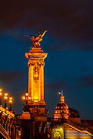 The ornate Pont Alexandre III (bridge) across the River Seine with its gilded sculptures featured winged horses behind and Hotel des Invalides in background, Paris, France.