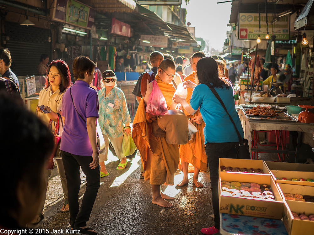 29 JUNE 2015 - BANGKOK, THAILAND: Buddhist monks on their alms round in Bang Chak Market. The Bang Chak Market serves the community around Sois 91-97 on Sukhumvit Road in the Bangkok suburbs. About half of the market has been torn down, vendors in the remaining part of the market said they expect to be evicted by the end of the year. The old market, and many of the small working class shophouses and apartments near the market are being being torn down. People who live in the area said condominiums are being built on the land.     PHOTO BY JACK KURTZ