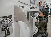 "Portland, Oregon, USA. 26 FEB, 2018. A performance artist cuts the work of the photographer Robert Frank from the wall at Blue Sky Gallery in Portland, Oregon, USA. The work was destroyed in a ""Destruction Dance"" performance defacing the photographs with ink and mutilation with scissors, knives and even ice skates  at the end of it's run. The destruction was Frank's protest regarding today's greed in the global art market."