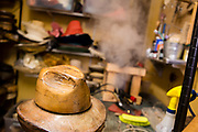 A wooden block made up of brim and crown sections ready for a hat to be shaped over it into a fedora. In the background, a straw hat body is being steamed.