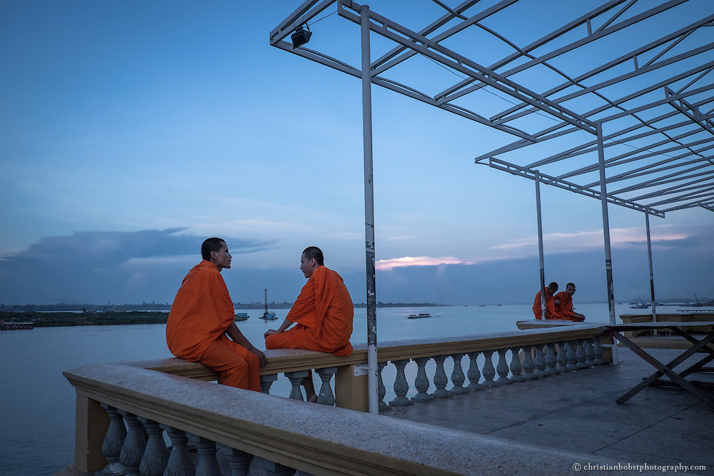 Buddhist monks enjoy the sunset at the riverfront of Tonle Sap in Phnom Penh.