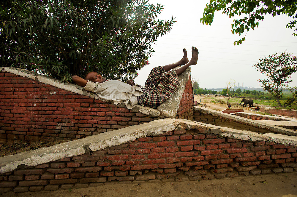26th March 2014,New Delhi. A man sleeps on a wall in New Delhi, India on the 26th March 2014<br /> <br /> Sleeping in the outdoors is common in Asia due to a warmer climate and the fact that personal privacy for sleep is not so culturally ingrained as it is in the West. New Delhi (where most of these images were taken) is a harsh city both in climate and environment and for those working long hours, often in hard manual labour, sleep and rest is something fallen into when exhaustion overwhelms, no matter the place or circumstance. Then there are the homeless, in Delhi figures for them from Government and NGO sources vary wildly from 25,000 to more than 10 times that. Others public sleepers may simply be travellers having a siesta along the way.<br />  <br /> <br /> PHOTOGRAPH BY AND COPYRIGHT OF SIMON DE TREY-WHITE, photographer in Delhi<br /> <br /> + 91 98103 99809<br /> email: simon@simondetreywhite.com
