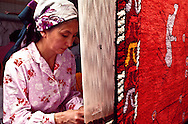 Nurzipha Zhangaziyeva weaves a modern-style carpet, based on ancient Kazakh petroglyphs, on a vertical loom at the Tamga carpet factory in Fabrichny in southeastern Kazakhstan.