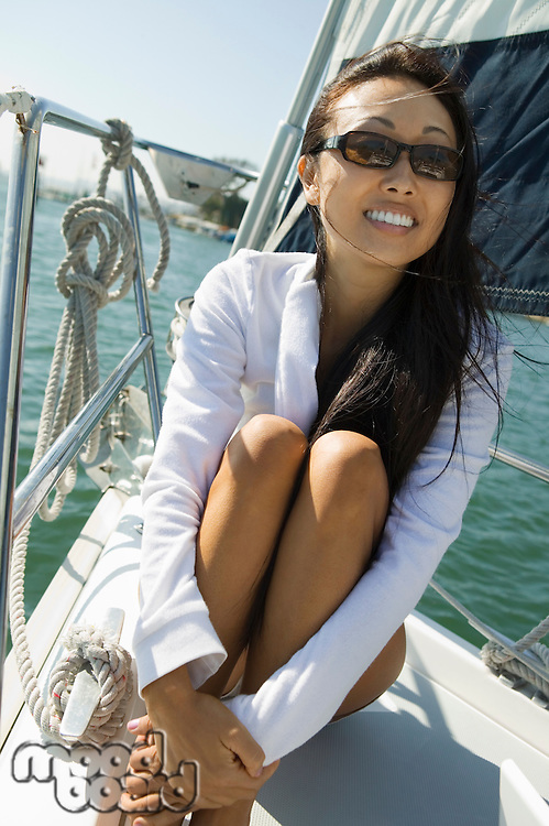 Woman in Sunglasses Sitting in Prow of Sailboat