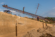Conveyor belts move sand from the dredging boats to the shore for drying. The dredged sand is sold locally and to large scale construction sites in nearby major cities such as Kunming and Jinhong.