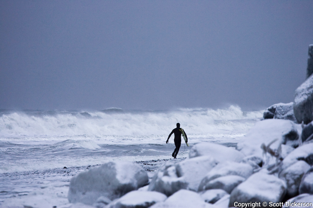 Alaskan surfer Gart Curtis runs across a snow covered beach carrying his surfboard to a stormy beach break in the dim winter light of a stormy afternoon in Homer, Alaska.