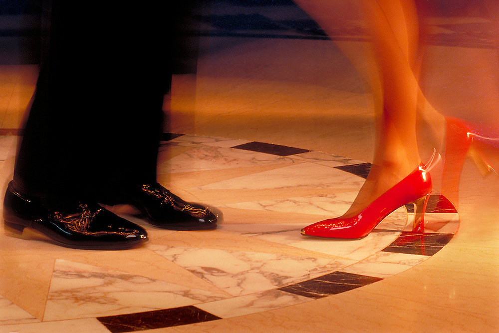 Formal footwear captured with motion blurr on marble dance floor.