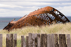 The rusted hull of the Ambassador lies on the beach in front of the abandoned Estancia San Gregorio on the Strait of Magellan in southern Chile.