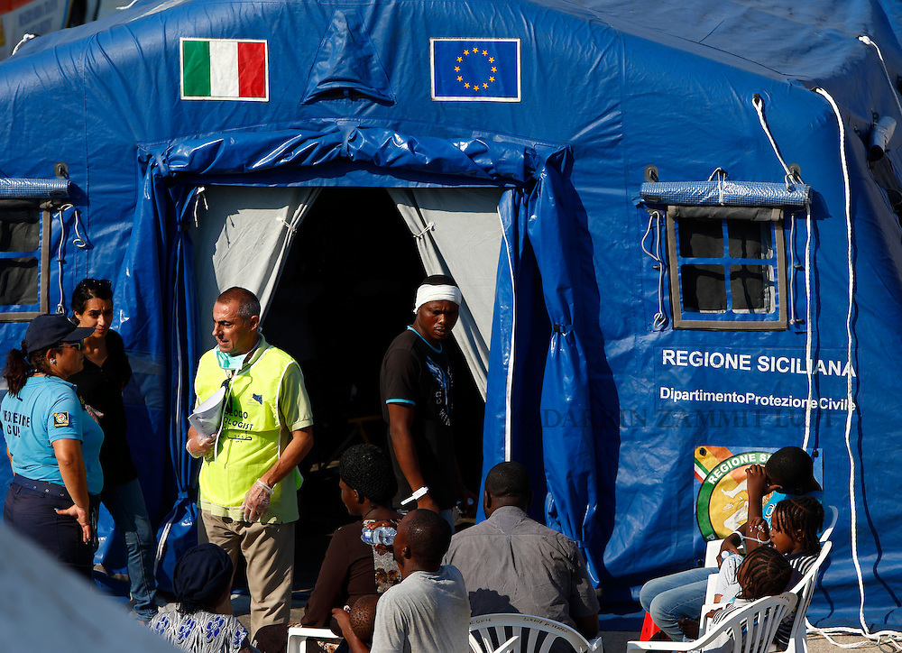 Migrants wait outside a Civil Protection tent after disembarking from line the Medecins san Frontiere (MSF) rescue ship Bourbon Argos in Trapani, on the island of Sicily, Italy, August 9, 2015.  Some 241 mostly West African migrants on the ship arrived on the Italian island of Sicily on Sunday morning, according to MSF.<br /> REUTERS/Darrin Zammit Lupi <br /> MALTA OUT. NO COMMERCIAL OR EDITORIAL SALES IN MALTA