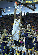 January 14, 2011: Iowa Hawkeyes forward Melsahn Basabe (1) puts up a shot between Michigan Wolverines guard Trey Burke (3) and Michigan Wolverines forward Blake McLimans (22) during the NCAA basketball game between the Michigan Wolverines and the Iowa Hawkeyes at Carver-Hawkeye Arena in Iowa City, Iowa on Saturday, January 14, 2011. Iowa defeated Michigan 75-59.