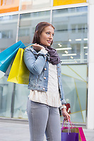 Young woman in casuals carrying shopping bags outdoors
