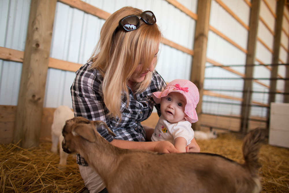 Danielle Raymond helps her daughter Olivia (8months) pet a goat during the Breakfast on the Farm event near Shedden, Ontario, Saturday, June 24, 2017.<br /> Farmers Forum/ Geoff Robins