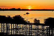 A sun rises as against a lobster boat and lobster traps in Beals Island, Maine.