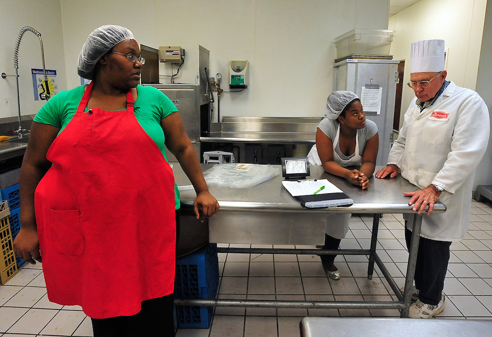 Lisia Sims, left, and Waynesha Lee talk with Chuck Clark at St. Philothea Greek Orthodox church as they wait for pans of freshly baked diner rolls to finish in the oven on Monday, June 21, 2010 in Watkinsville, Ga.  .