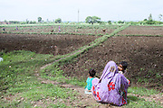 A woman and her two children are sitting next to a field in the rural area outside of Varanasi, Uttar Pradesh, India.